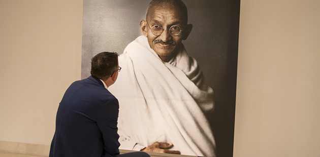 Premier Daniel Andrews sits in front of a portrait of Mahatma Gandhi in Delhi