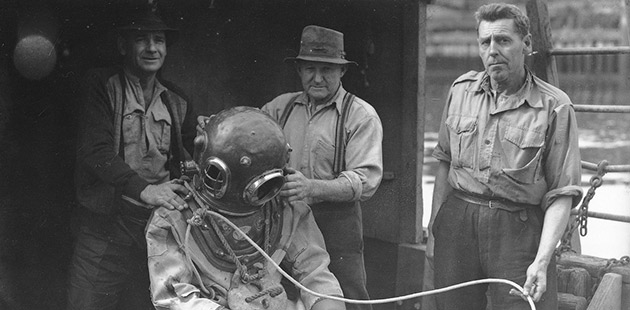 SLM ATW Hard hat diver preparing to enter water from the Maritime Services Board diver's punt - courtesy of NSW State Archives